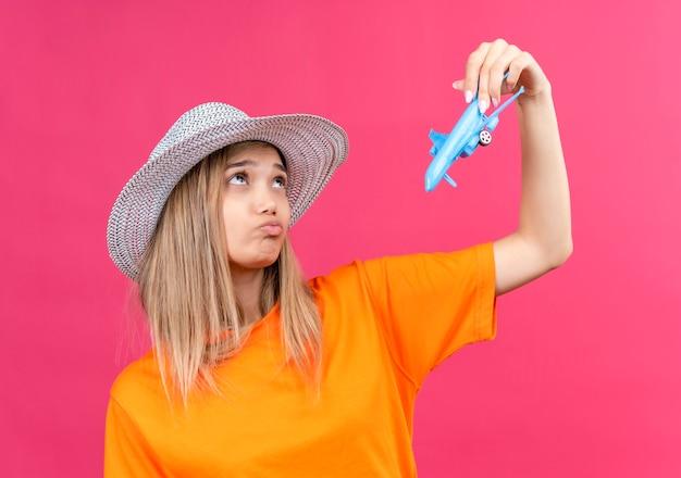 Een mooie jonge vrouw in een oranje t-shirt met zonnehoed die droomt over het vliegen van een vliegtuig terwijl ze een blauw speelgoedvliegtuig op een roze muur vasthoudt