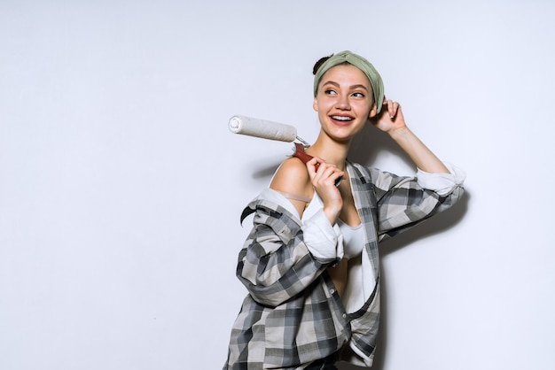 Een mooie jonge vrouw in een overhemd schildert de muren met een roller in haar nieuwe appartement