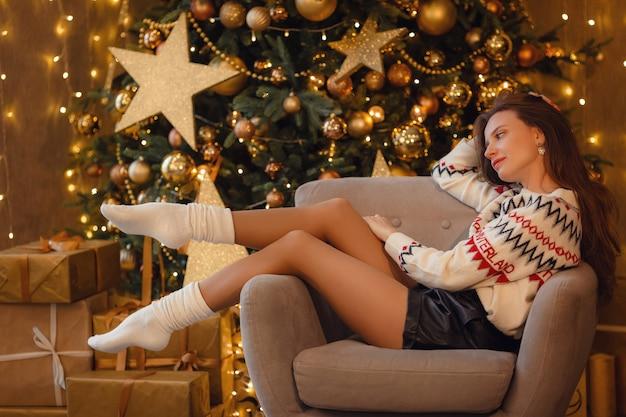 Een mooie jonge vrouw in een trui zit te wachten op een vakantie in de buurt van de nieuwjaarsboom versierd met gouden slingers en kerstversieringen. het idee en concept van kerstmis en nieuwjaar