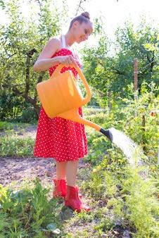 Een mooie jonge vrouw in een vintage jurk de planten in de tuin water geven.