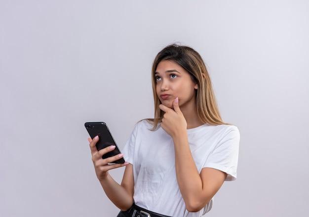Een mooie jonge vrouw in een wit t-shirt denken terwijl ze mobiele telefoon vasthoudt op een witte muur Gratis Foto