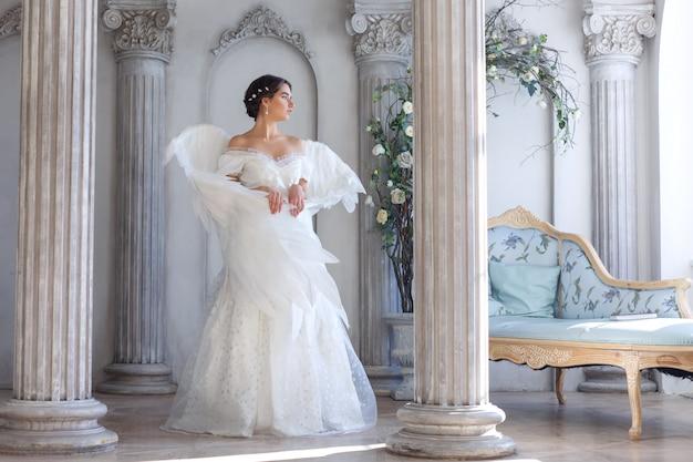 Een mooie jonge vrouw in een witte jurk met engelenvleugels op haar rug. het staat in een prachtig decor tegen de muur.
