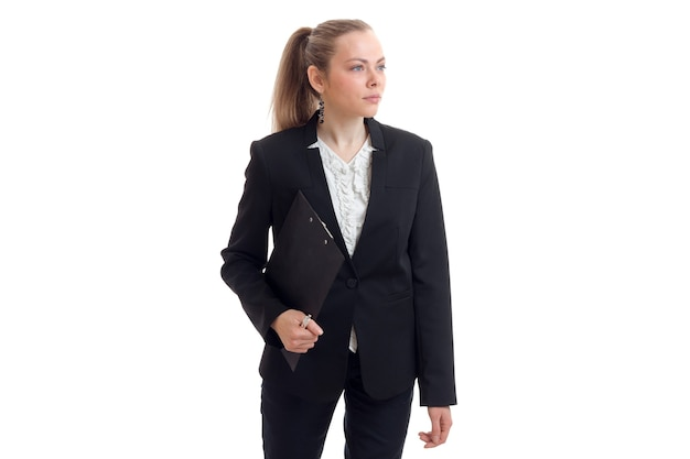 Een mooie jonge vrouw in een zwart pak kijkt weg en houdt de tablet op een witte muur