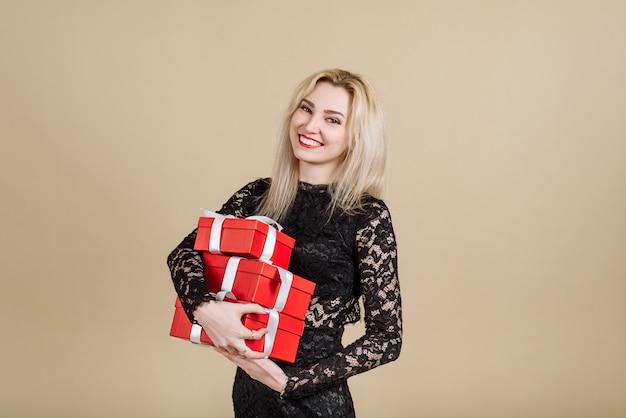 Een mooie jonge vrouw in een zwarte jurk houdt een bos rode geschenken in haar handen. het concept van de vakantie, het geven van geschenken.