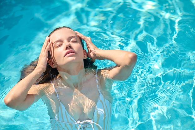 Een mooie jonge vrouw in een zwembad die er sensueel en aantrekkelijk uitziet