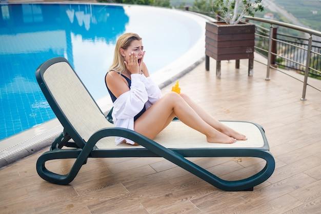 Een mooie jonge vrouw in een zwempak en een wit overhemd zit op een ligstoel bij het zwembad en wrijft haar lichaam in met zonnebrandcrème. zomerse huidverzorging, bescherming tegen huidverbranding