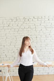 Een mooie jonge vrouw in elegante zakelijke kleding staat voor een tafel met grafieken en diagrammen.