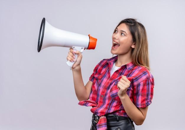 Een mooie jonge vrouw in geruit overhemd die door megafoon op een witte muur spreekt