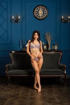 Een mooie jonge vrouw in ondergoed zit half gedraaid op het bed. het concept van de ochtend van de bruid.