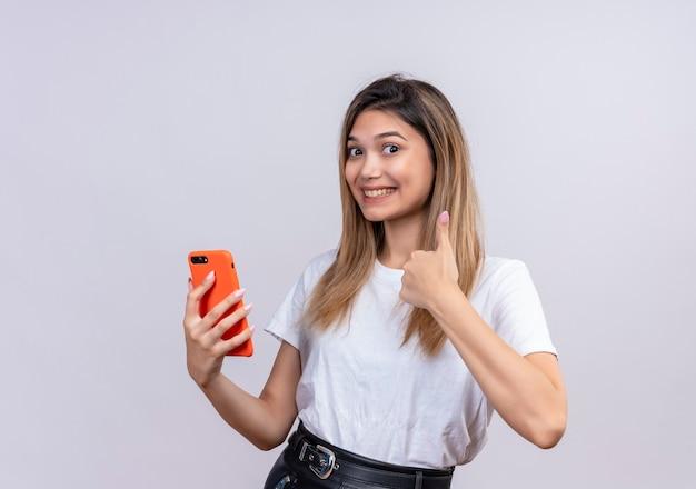 Een mooie jonge vrouw in wit t-shirt duimen opdagen terwijl ze mobiele telefoon vasthoudt op een witte muur