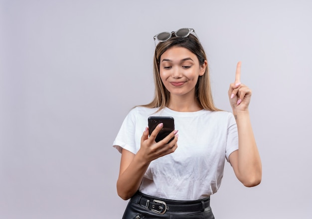 Een mooie jonge vrouw in wit t-shirt met zonnebril op haar hoofd wijzend met wijsvinger tijdens het kijken naar mobiele telefoon op een witte muur
