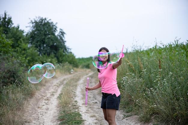 Een mooie jonge vrouw lanceert enorme zeepbellen op de achtergrond prachtige natuur.