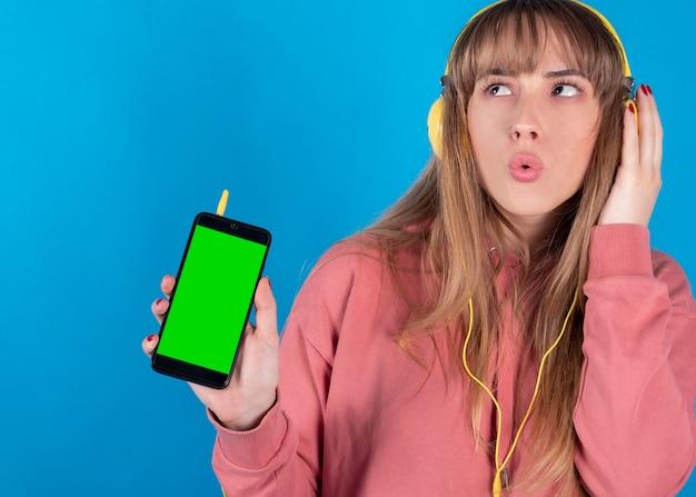 Een mooie jonge vrouw luistert naar muziek met koptelefoon en zonnebril, chromen mobiele scherm
