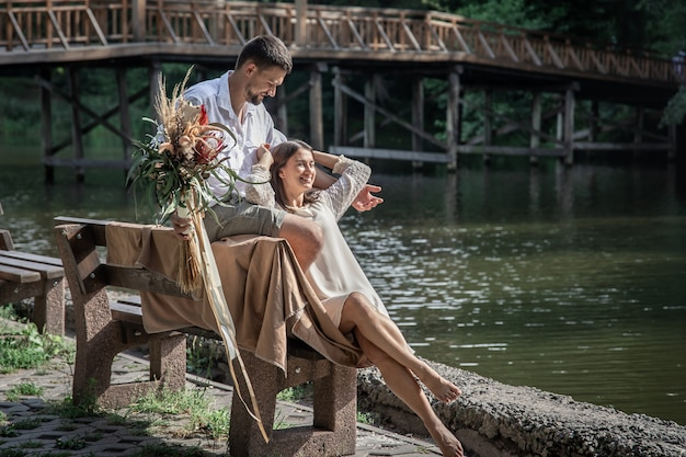 Een mooie jonge vrouw met bloemen en haar man zitten op een bankje en genieten van communicatie, een date in de natuur, romantiek in het huwelijk.