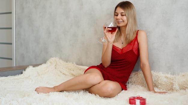 Een mooie jonge vrouw met een glimlach zit in rood ondergoed op een witte plaid met wijn in haar hand. valentijnsdag ochtend