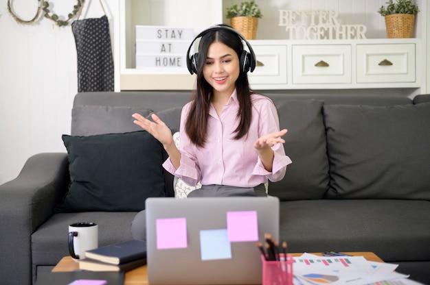 Een mooie jonge vrouw met een hoofdtelefoon voert thuis een videoconferentiegesprek via de computer tijdens de coronaviruspandemie