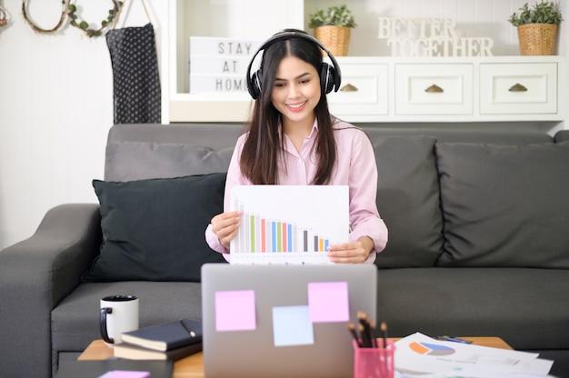 Een mooie jonge vrouw met hoofdtelefoon maakt thuis videoconferentiegesprek via computer, bedrijfstechnologieconcept.