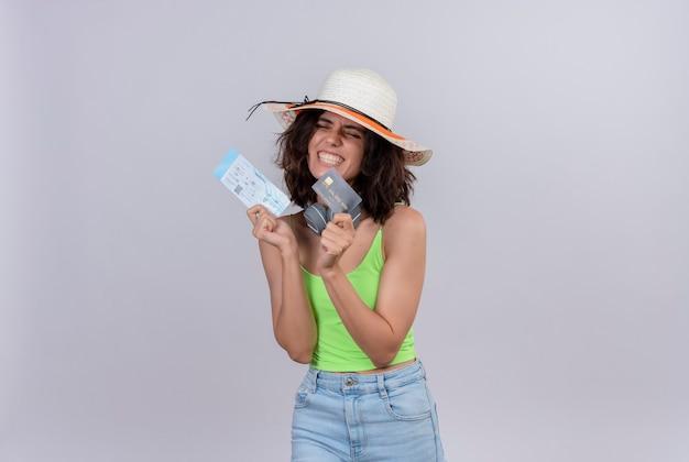 Een mooie jonge vrouw met kort haar in een groene crop top draagt een zonnehoed met vliegtickets en een creditcard met gesloten ogen op een witte achtergrond
