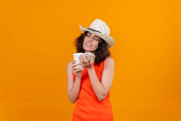 Een mooie jonge vrouw met kort haar in een oranje overhemd met een zonnehoed die geniet van de geur van koffie