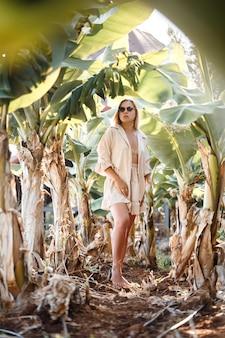 Een mooie jonge vrouw met lang blond haar van europees uiterlijk staat in de buurt van de bananenbomen. meisje in tropisch woud op een zonnige zomerdag