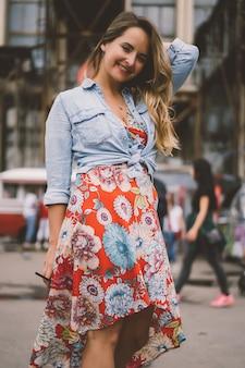 Een mooie jonge vrouw met lang haar met een glas koffie lacht en lacht.