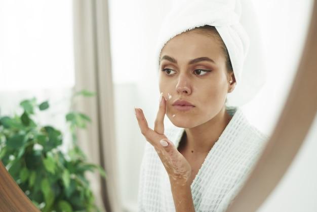 Een mooie jonge vrouw met vitiligo op haar handen in een badjas brengt een crème aan op haar gezicht