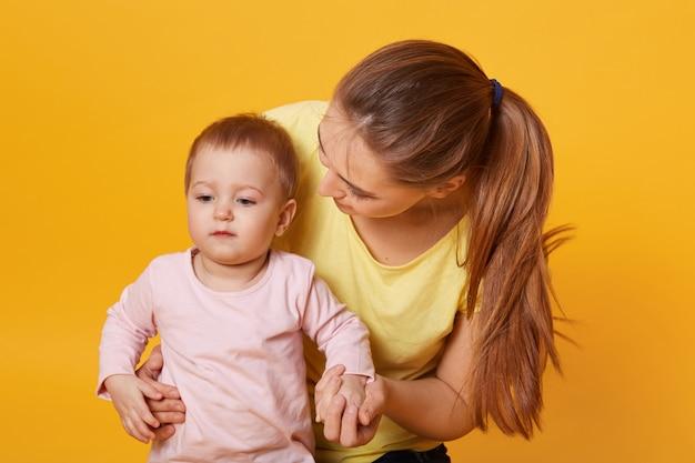 Een mooie jonge vrouw omhelst haar lieve ernstige kind