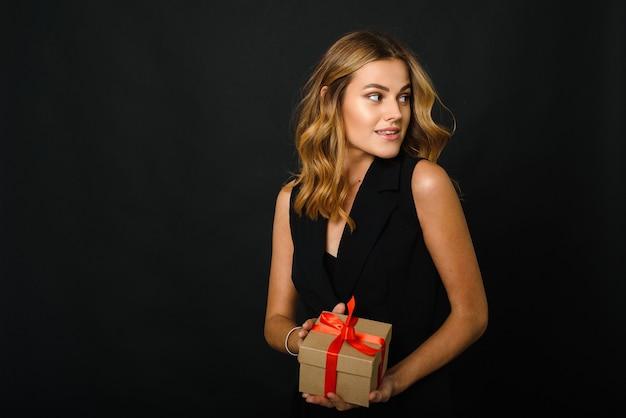 Een mooie jonge vrouw op een zwarte achtergrond met een kerstcadeau.