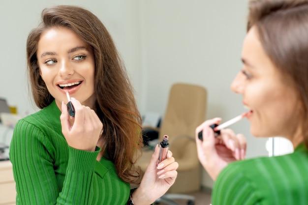 Een mooie jonge vrouw past lippenstift toe op haar lippen in de spiegel kijken