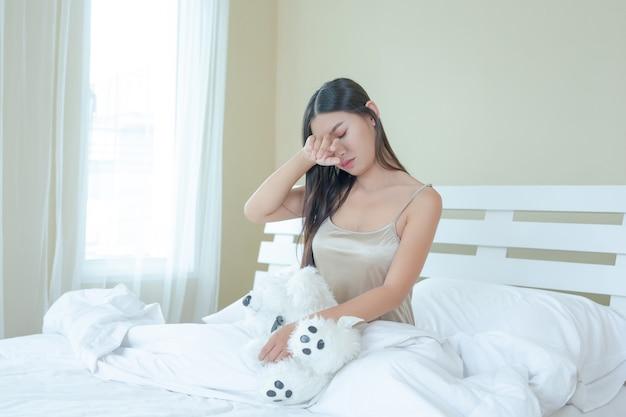 Een mooie jonge vrouw slaapt thuis en een wekker in de slaapkamer.