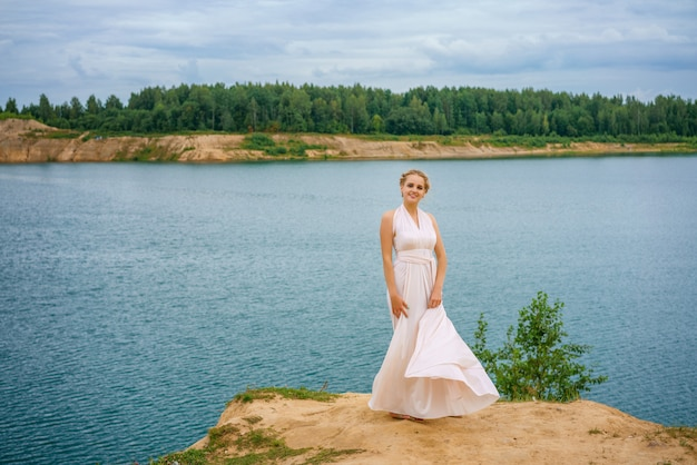 Een mooie jonge vrouw staat in een mooie jurk op een klif