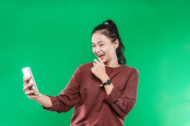 Een mooie jonge vrouw voert een videogesprek met iemand die haar kin vasthoudt en lacht met een blije uitdrukking op een groene achtergrond