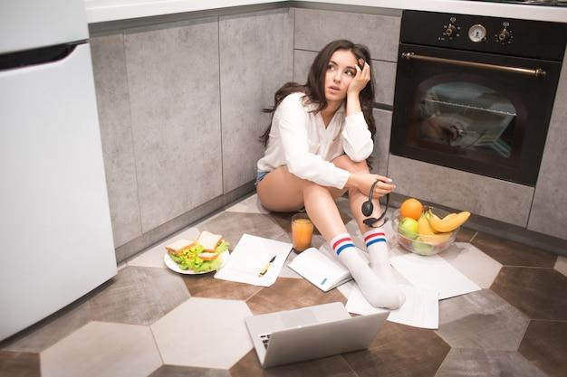 Een mooie jonge vrouw werkt de hele nacht in de keuken van haar huis, ze is erg moe.