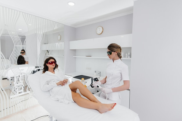 Een mooie jonge vrouw zal laser ontharing ondergaan met moderne apparatuur in een spa salon. schoonheidssalon