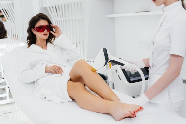 Een mooie jonge vrouw zal laser ontharing ondergaan met moderne apparatuur in een spa salon.