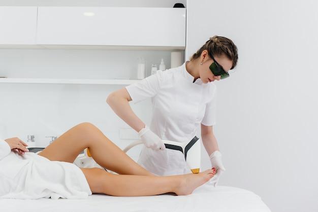 Een mooie jonge vrouw zal laser ontharing ondergaan met moderne apparatuur in een spa salon