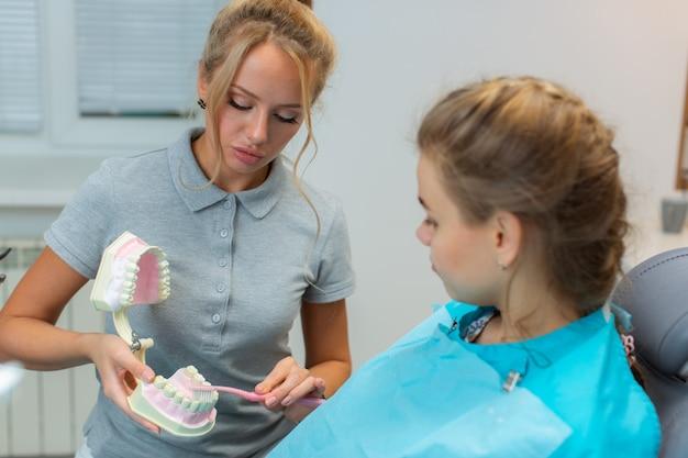 Een mooie jonge vrouwelijke tandarts legt aan een meisjespatiënt uit over mondhygiëne