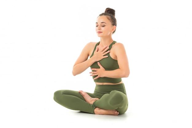 Een mooie jonge vrouwelijke turnster met donker lang haar gevuld in een bundel in een groen sport-elastische pak zit en ademt.