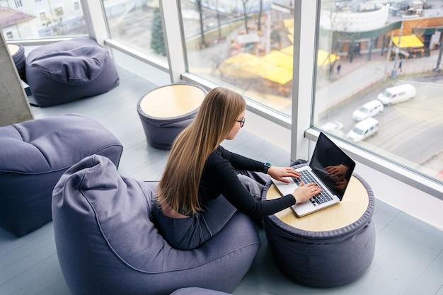 Een mooie jonge vrouwenmanager zit met laptop op een zachte poef dichtbij het panoramische venster. meisjeszakenman die aan een nieuw project werkt