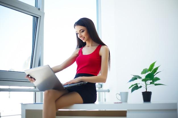 Een mooie jonge zakenvrouw met behulp van een laptop