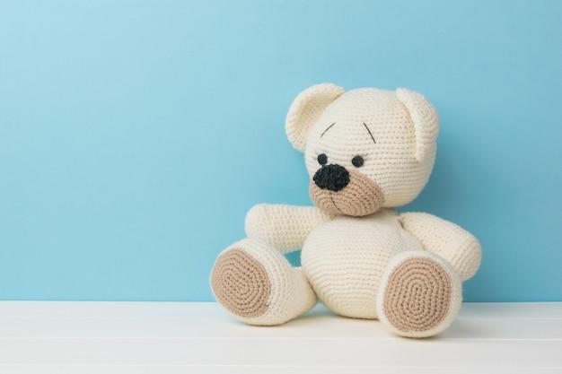 Een mooie kleine gebreide teddybeer op een witte tafel op een blauwe achtergrond.