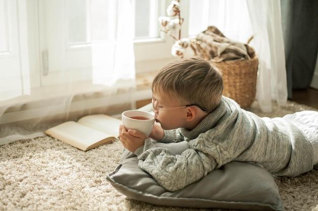 Een mooie kleine jongen in een gebreide trui leest bij het raam met een mok hete thee. knus. herfst. valstemming.