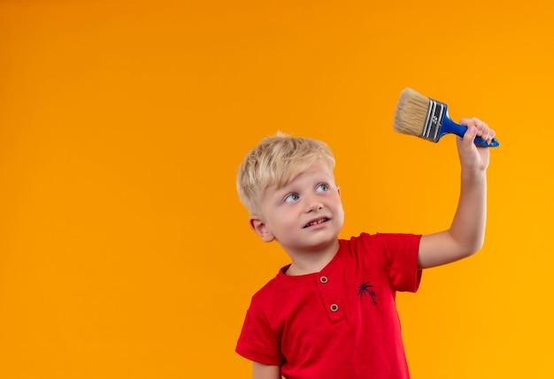 Een mooie kleine jongen met blond haar en blauwe ogen die een rood t-shirt dragen dat een blauwe verfborstel opheft en ernaar kijkt op een gele muur