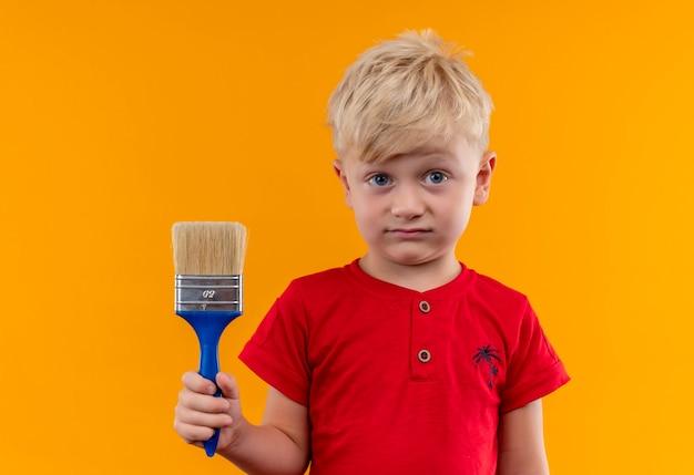 Een mooie kleine jongen met blond haar en blauwe ogen, gekleed in een rood t-shirt met blauwe verfborstel op zoek op een gele muur