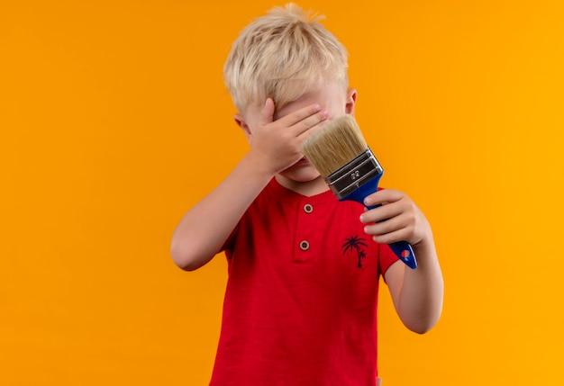 Een mooie kleine jongen met blond haar, gekleed in een rood t-shirt met blauwe verfborstel met hand bedekkende ogen op een gele muur