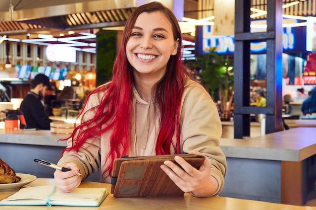 Een mooie lachende vrouw met rood haar werkt op afstand in een café en houdt een tablet in haar hand kijkt vrolijk naar de camera