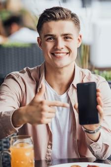Een mooie man brengt zijn tijd door met telefoon en bier