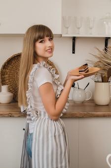 Een mooie meisjeshuisvrouw in een grijs schort staat in de keuken en houdt een bord met dessert vast