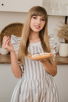 Een mooie meisjespatissier of huisvrouw houdt een bord met eclairs en banketbakkerstang vast