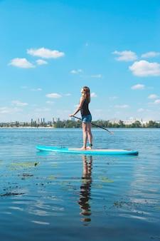 Een mooie millennial vrouw staat midden op de rivier op een sup board